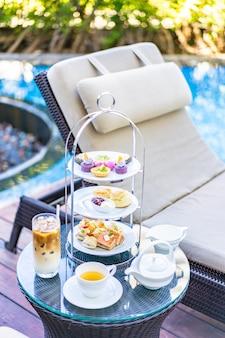 Nachmittagstee-set mit latte-kaffee und heißem tee auf dem tisch in der nähe des stuhls um den pool