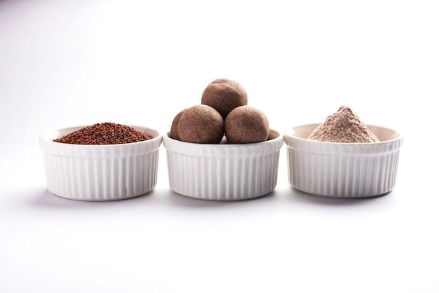 Nachni laddu oder ragi laddoo oder bällchen aus fingerhirse, zucker und ghee. es ist ein gesundes essen aus indien. serviert in einer schüssel oder einem teller mit rohem ganzen und pulver. selektiver fokus