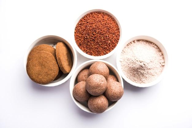 Nachni oder ragi laddu und kekse oder kekse aus fingerhirse, zucker und ghee. es ist ein gesundes essen aus indien. serviert in einer schüssel oder einem teller mit rohem ganzen und pulver