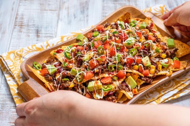 Nacho maistortillachips mit käse, fleisch, guacamole und glühender würziger salsa