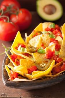 Nachos beladen mit salsa, käse und jalapeno