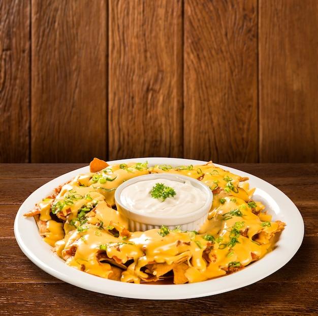 Nachos-chips mit cheddar-käse und dips auf dem teller.