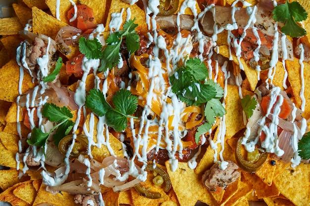 Nachos - eine klassische mexikanische vorspeise aus maistortillachips. nachos mit saucen und holopenya. draufsicht. nahansicht.