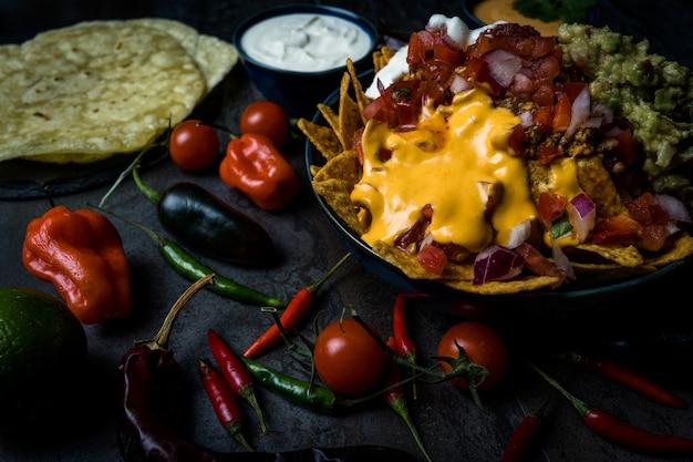 Nachos im darkfood-stil mit cheddar-käse-sauerrahm und pico de gallo