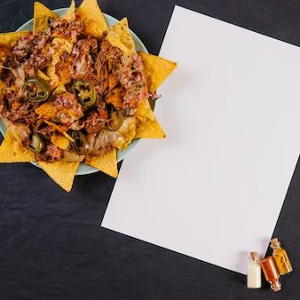 Nachos in der nähe von papierblatt