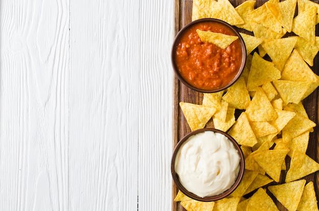 Nachos-maischips mit würzigen tomaten-käse-saucen.