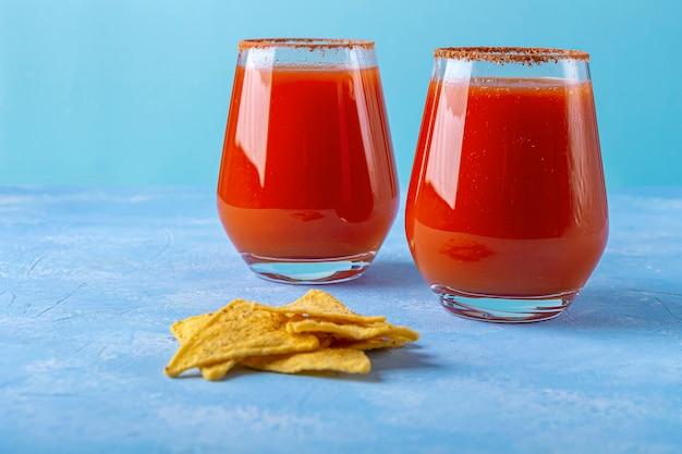 Nachos, maistortillachips mit würziger sauce und alkoholischem getränk michelada. cocktail mit tomatensaft und bier