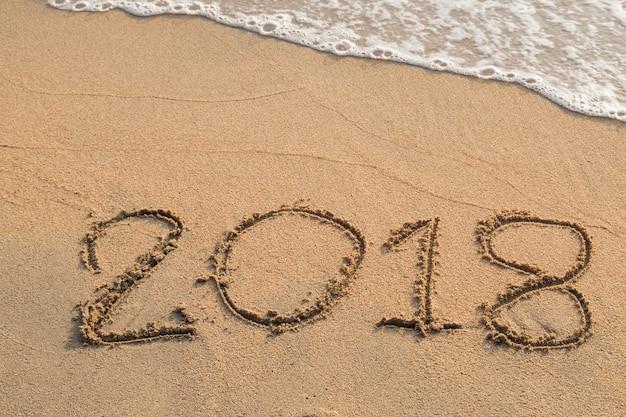 Nachricht 2018 geschrieben in den sand am strandhintergrund