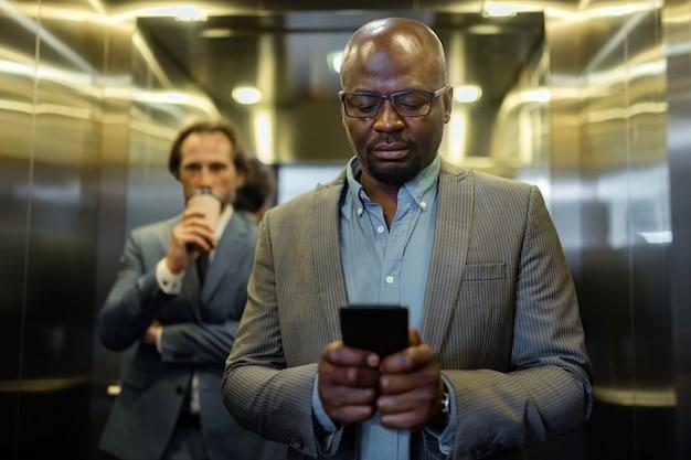 Nachricht lesen. dunkelhäutiger geschäftsmann mit brille, der nachricht auf dem smartphone liest reading