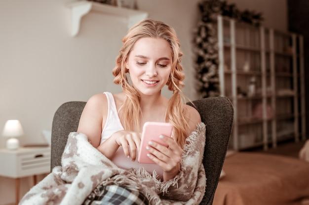 Nachrichten überprüfen. zufriedene dame mit komplizierter frisur, die spaß mit smartphone hat, während wintermorgen zu hause verbracht wird