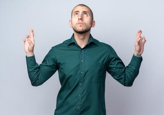 Nachschlagen junger gutaussehender kerl mit grünem hemd, das die finger kreuzt