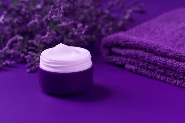 Nacht-anti-falten-anti-aging-creme-körperpflege und gesichtspflege-hygiene-feuchtigkeitslotion mit lila blüten in plastikglas mit handtuch auf lila hintergrund.