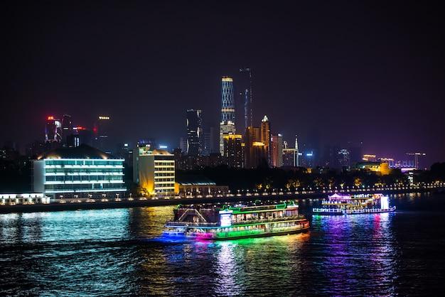 Nachtansicht der stadt mit schiffen auf dem wasser