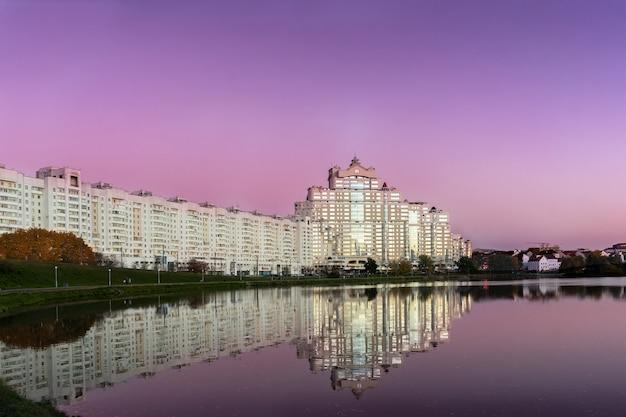 Nachtansicht des historischen zentrums von minsk, weißrussland. haus im sonnenuntergang im wasser mit reflexion. herbstzeit des jahres