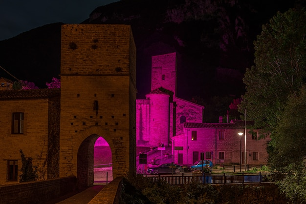 Nachtansicht des mittelalterlichen dorfes am fluss, san vittore frasassi, marken, italien. romantischer himmel und wolken über berglandschaft, tourismusziel.