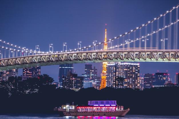 Nachtansicht rainbow bridge und tokyo tower. die kreuzfahrt ist in der bucht von tokyo, odaiba in der nacht, japan, gesegelt