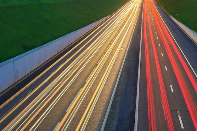 Nachtautobahnstraße mit autolichtern gelbe und rote lichtspur auf der straße mit geschwindigkeitsverkehr. langzeitbelichtung abstrakter urbaner hintergrund