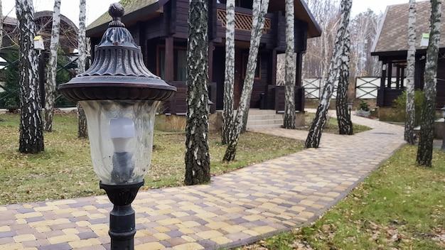 Nachtbeleuchtung von wanderwegen auf der straße für spaziergänge in einem landhotel mit holzhäusern im wald. kleine solarlampe im retro-stil mit bewegungsmelder im innenhof des stadthauses.