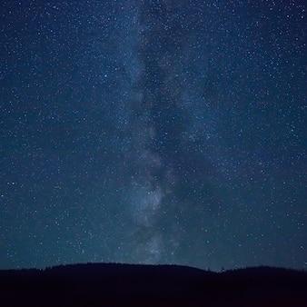 Nachtblauer himmel mit vielen sternen und milchstraße über einem berg Premium Fotos