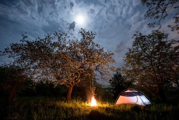 Nachtcamping. belichtetes touristisches zelt nahe lagerfeuer unter bäumen und nächtlichem himmel mit dem mond