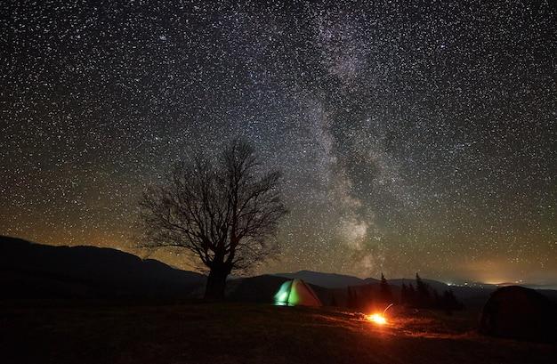 Nachtcamping im gebirgstal unter sternenhimmel