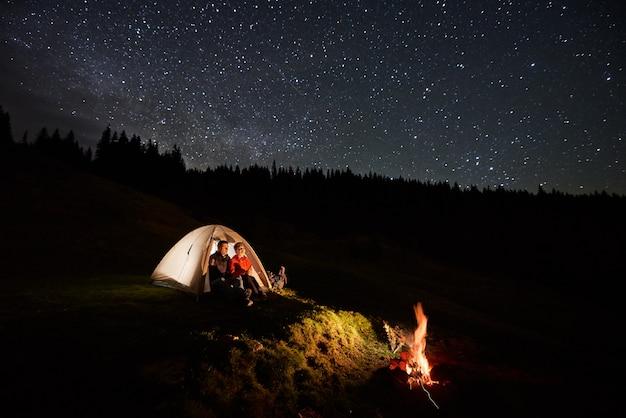Nachtcamping in den bergen. paartouristen ruhen sich im beleuchteten zelt am lagerfeuer unter dem sternenhimmel aus