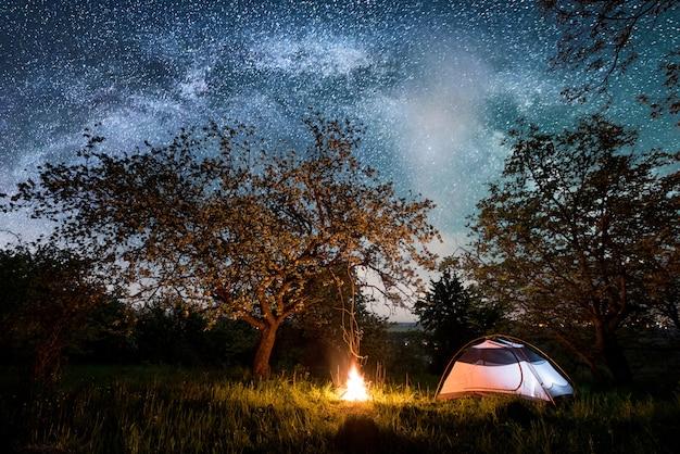 Nachtcamping in der nähe der stadt. beleuchtetes touristenzelt in der nähe von lagerfeuer unter bäumen und wunderschönem nachthimmel voller sterne und milchstraße