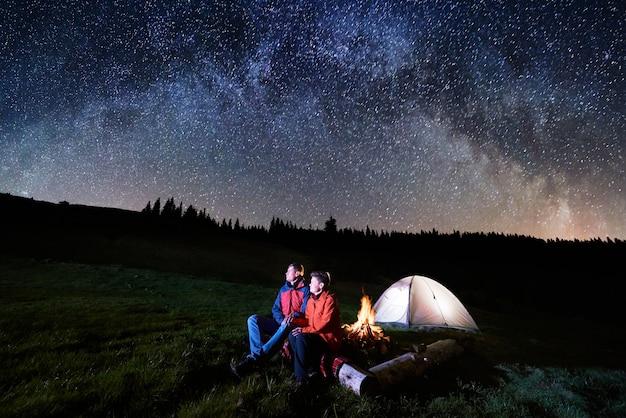 Nachtcamping. mann- und frauentouristen ruhen sich am lagerfeuer in der nähe des beleuchteten zeltes aus