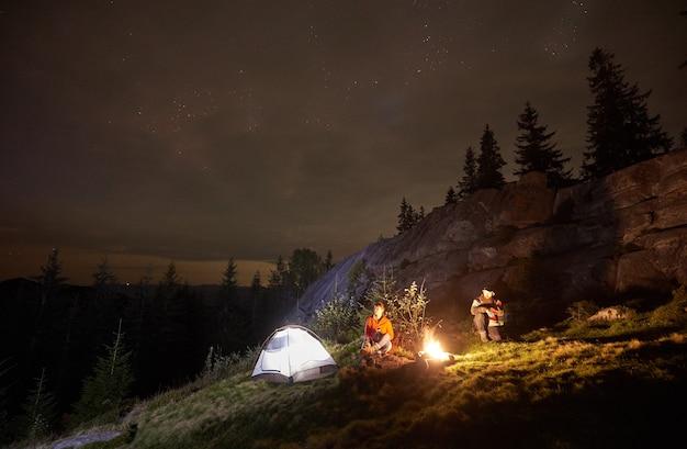 Nachtcamping mit menschen am lagerfeuer unter nächtlichem sternenhimmel