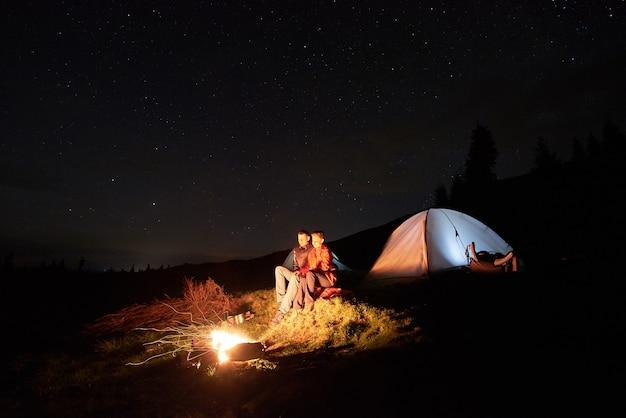 Nachtcamping. romantische paartouristen ruhen sich am lagerfeuer in der nähe eines beleuchteten zeltes unter dem sternenhimmel aus