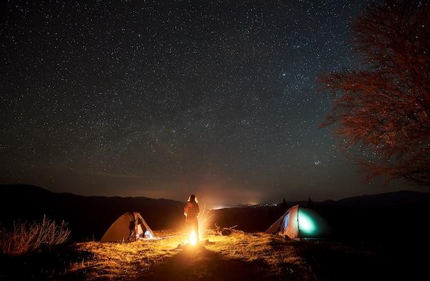 Nachtcamping. wanderer, der nahe lagerfeuer unter sternenhimmel ruht