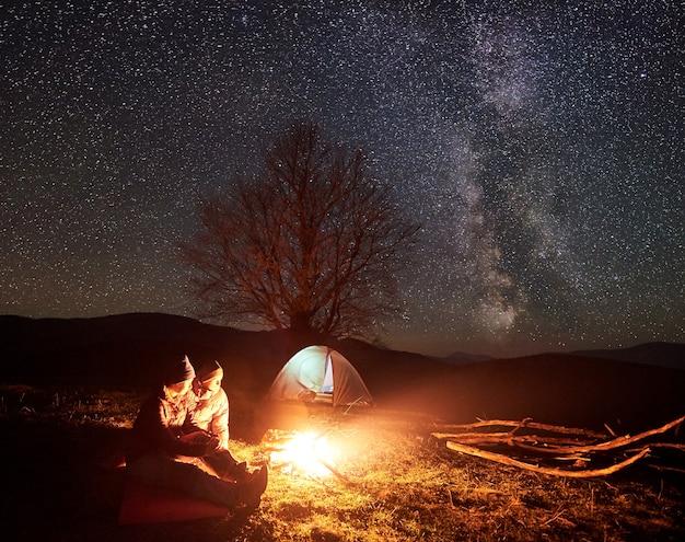 Nachtcamping. wanderer ruhen am lagerfeuer unter sternenhimmel