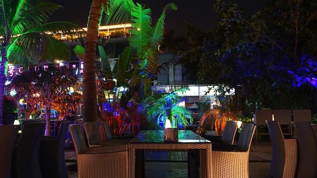 Nachtclub, bar, café. nachts tropische beach club bar mit lila, grünen und blauen lichtern