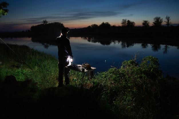 Nachtfischen, fischer mit einer angelrute am ufer des sees.