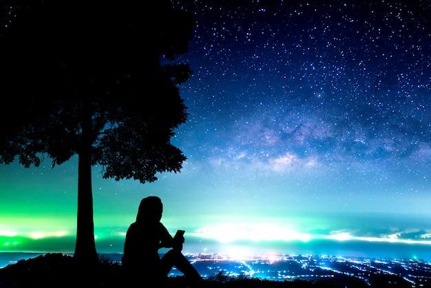 Nachthimmel mit milchstraßensternen und stadtlichtern