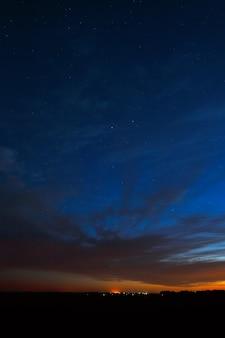 Nachthimmel mit sternen. ein heller sonnenuntergang mit wolken. kosmischer raum über der erdoberfläche. langzeitbelichtung.