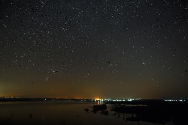 Nachthimmel mit sternen über dem fluss während der frühjahrsflut. blick in den sternenhimmel.