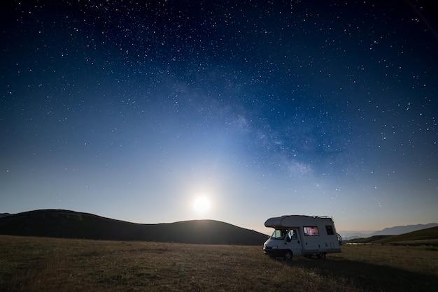 Nachthimmel über campo imperatore hochland, abruzzen, italien. die milchstraße und sterne bei mondlicht über beleuchtetem wohnmobil.
