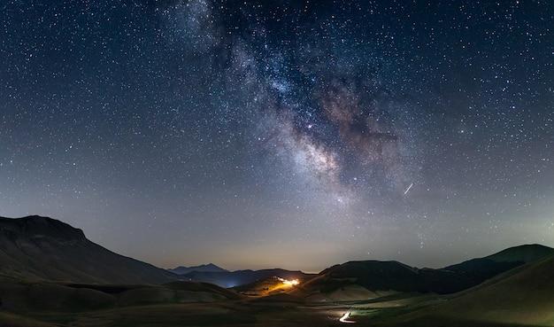 Nachthimmel über dem hochland von castelluccio di norcia, italien. der kern der milchstraße und die sterne über der beleuchteten einzigartigen hügellandschaft des dorfes.