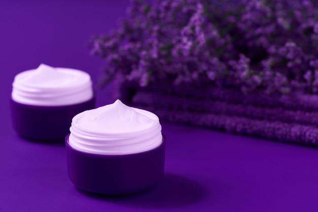 Nachthygienisches creme-hautpflegeprodukt in violettem plastikglas mit handtuch auf dem tisch. hautreinigende kosmetische creme oder vitamin-spa-lotion, eine natürliche organische kräuter-anti-falten-feuchtigkeitscreme.