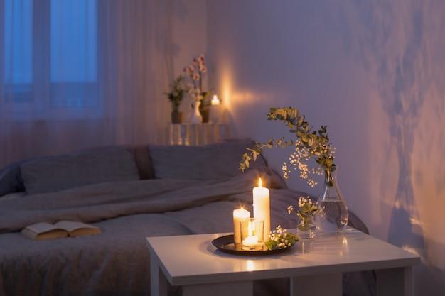 Nachtinnenraum des schlafzimmers mit blumen und brennenden kerzen
