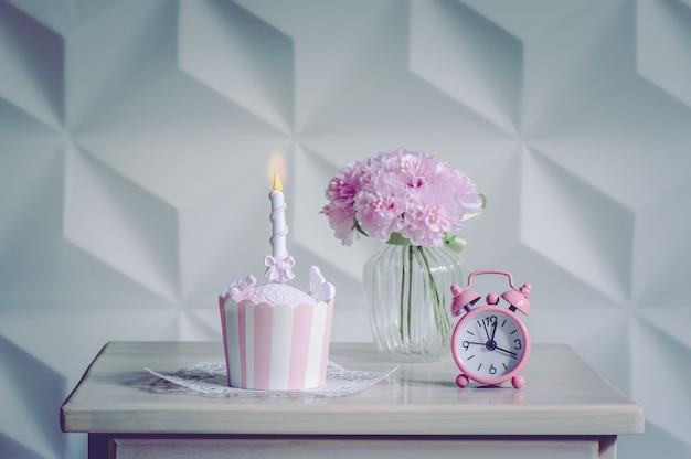 Nachtisch des geburtstagskleinen kuchens und rosa blumen mit wecker für partei