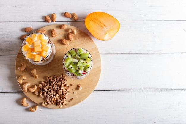 Nachtisch mit griechischem joghurt, granola, mandel, acajoubaum, kiwi und persimone auf weißem hölzernem.