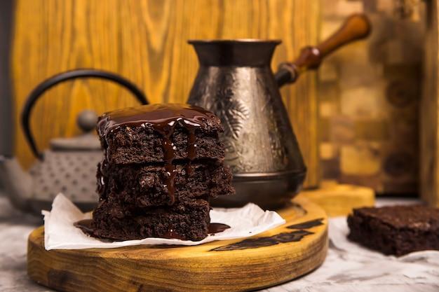 Nachtisch mit kakaoschokoladenkuchen in der schokolade nahe teetopf und kaffeetürke