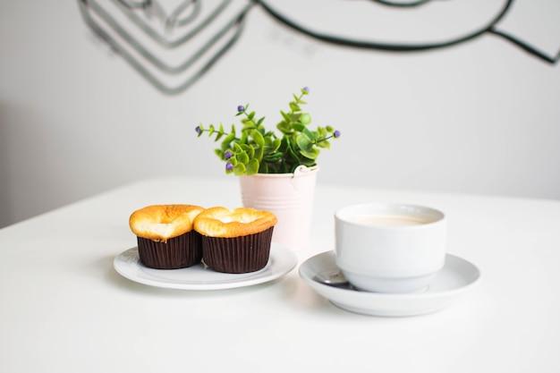 Nachtisch und kaffee am café mit plastikanlage im vase auf weißer tabelle.