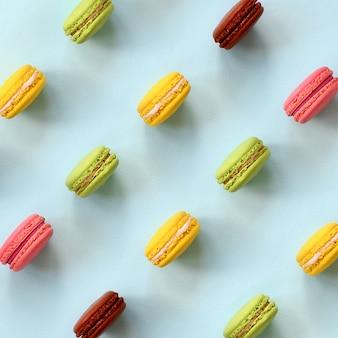 Nachtischkuchen macaron oder makrone auf draufsicht des modischen blauen pastellhintergrundes. flat lay zusammensetzung