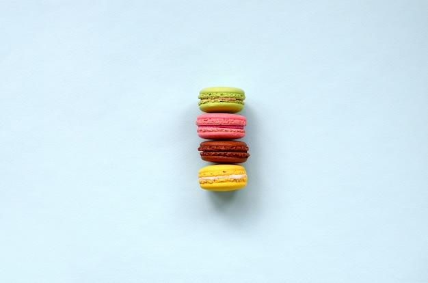Nachtischkuchen macaron oder makrone auf draufsicht des modischen blauen pastellhintergrundes.