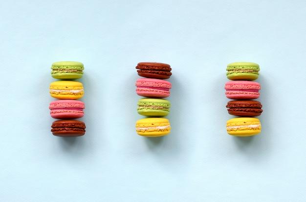 Nachtischkuchen macaron oder makrone auf draufsicht des modischen blauen pastellhintergrundes