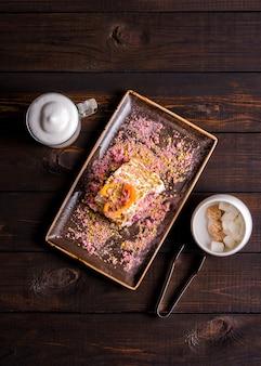 Nachtischmeringebrötchen mit pistazien und blaubeeren, cappuccino und zucker auf dunklem hintergrund.
