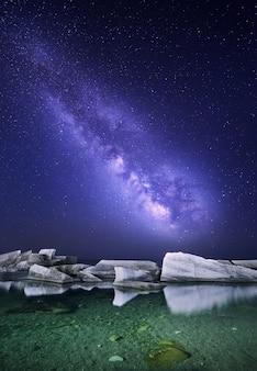 Nachtlandschaft mit bunter milchstraße in dem meer mit steinen. sternenklarer himmel. raum hintergrund